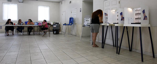 Melissa Morales, right, votes at the Tenrikyo Mission in the Boyle Heights area of Los Angeles.