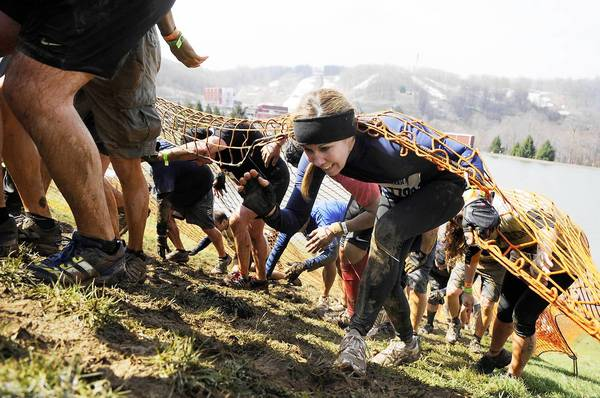 Participants climb up a steep hill in the mud under a net in the Tough Mudder Challenge at Bear Creek Resort in 2011.