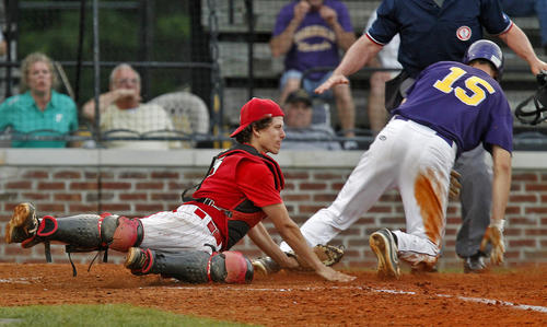 Menchville's Austin Fields ,right, crosses home palte before the tag from Hampton catcher Graham Johnson during Wednesday's game.