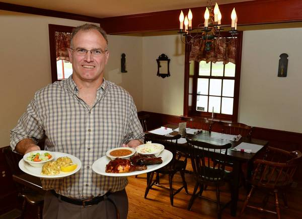 Owner Dan Tanczos holds entrees Blue Mountain Crab Cakes (left) and the Smokehouse Sampler in one of the dinning rooms at the Point Phillips Hotel in Bath.