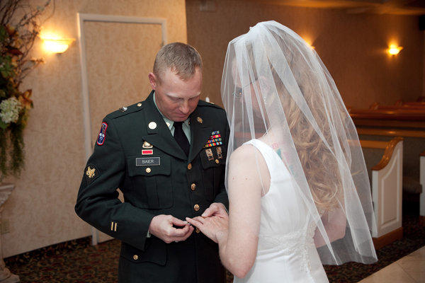 Jason Baier puts a ring on his bride's finger during a ceremony at Victoria's Wedding Chapel in Las Vegas. The chapel is offering service members and veterans free weddings from noon to 8 p.m. on Memorial Day.