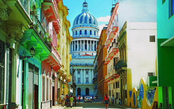 A street scene in Havana; in the background is the landmark El Capitolio.