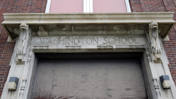 A sign, faded by time, hangs over the door on the south side of the vacant Washington School. photo by john davis taken 5/22/2013