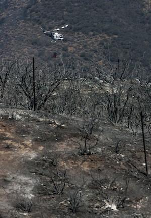 Trails reopen Friday at Point Mugu State Park, where visitors can expect to see areas torched by the Springs fire. Above, a helicopter gets ready to drop water on a hot spot on May 4.