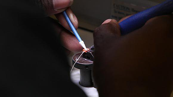 A Knowles worker assembles a microphone product in the micro prototype lab, at Knowles research and development facility in Itasca in 2011. (Antonio Perez/ Chicago Tribune)