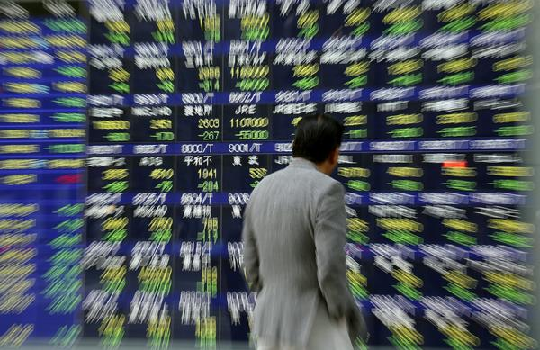 A Tokyo pedestrian eyes an electronic screen displaying stock quotes as the dramatic drop in Japan's Nikkei stock index unfolds on Thursday.