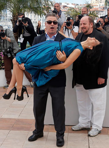 "Cast member Alec Baldwin carries his wife Hilaria Thomas during a photocall for the film ""Seduced and Abandoned"" at the 66th Cannes Film Festival in Cannes May 21, 2013."