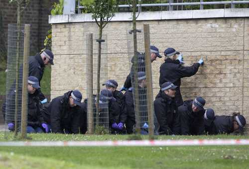 A police forensics team searches a crime scene for evidence, where a man was killed the day before in Woolwich, southeast London May 23, 2013. British authorities believe that two men accused of hacking a soldier to death on a London street in revenge for wars in Muslim countries are British of Nigerian descent, a source close to the investigation said Thursday.
