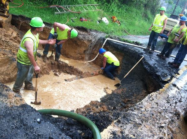 Easton suburban water authority workers fix a broken water pipe on Northwood Ave in a downpour on Thursday morning. The broken pipe caused a sinkhole that has closed Northwood Avenue closed from Tatamy Road to East Lane in Palmer Township.