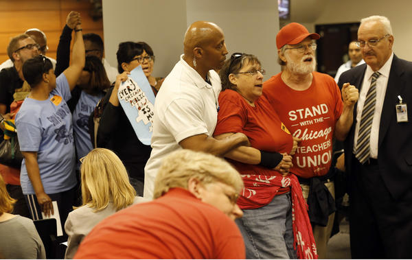 Protesters are led from the Chicago Board of Education meeting after causing disruptions.