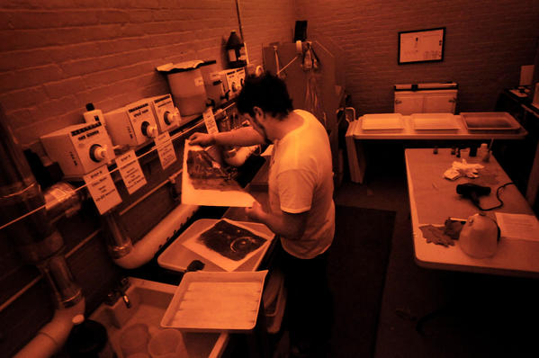 Joe McCarthy of Middletown works on kallitype prints in the amber-lit darkroom at Photosynthesis, a photographic arts and services center in Manchester.