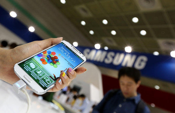 An event employee displays a Samsung Electronics Co. Galaxy S4 smartphone at the World IT Show 2013 in Seoul, South Korea, on Tuesday.