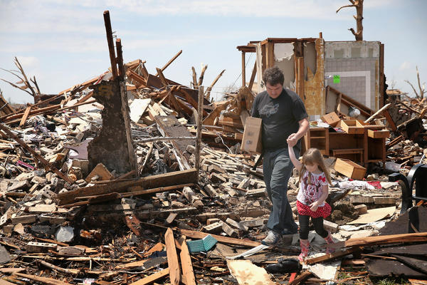 Lee Haskins leaves his house, which was destroyed by Monday's tornado, with his daughter Elizabeth Haskins, 4, after recovering a few items in Moore, Okla.