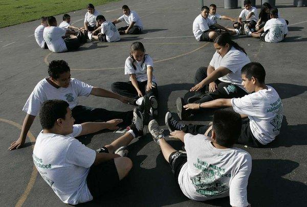 Sixth-graders stretch at Van Nuys Middle School in gym class. In a new report, the Institute of Medicine urges programs to give kids more and better exercise -- in and out of school.