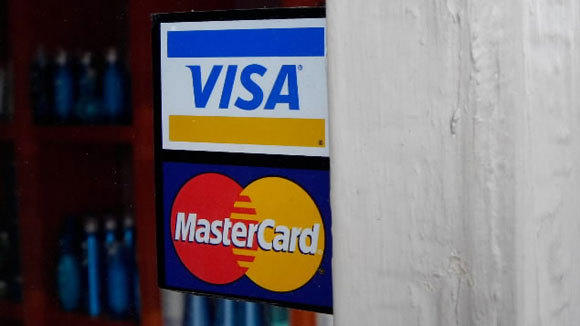 A sign for Visa and MasterCard adorn the window of a San Francisco retailer in a 2008 file photo.