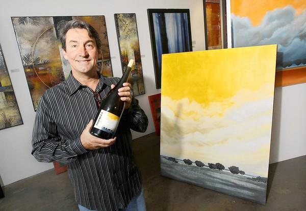 "Townley Gallery's Marketing and Sales Director Bill Bradfield, right, stands next to ""Pinot Sky,"" the same artwork that's on the Townley white wine label."