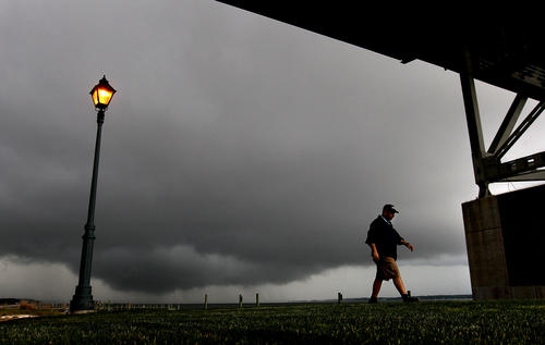 Joseph Nasra takes a walk along the Yorktown waterfront under the Coleman Bridge as thunderstorms make their way into the area Thursday evening.