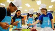Wearing pint-sized chef hats and aprons, a gaggle of elementary-schoolers looks up expectantly from picked-clean plates.