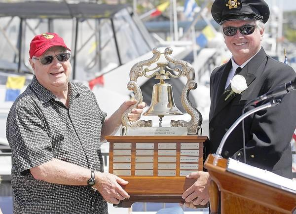 Doug Campbell, left, a member of the Balboa Yacht Club, poses for a photo with Bahia Corinthian Yacht Club commodore Tom Madden after accepting the 2013 Edward F. Kennedy memorial trophy during opening day for the Bahia Corinthian Yacht Club on May 11.