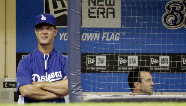 Dodgers manager Don Mattingly watches from the dugout during the first inning of a game against the Milwaukee Brewers.