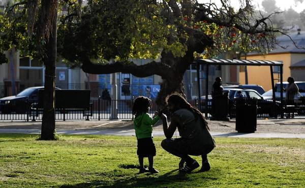 Ankh Sa Roots talks with his son Ajahni, 3, in Leimert Park. When the South L.A. neighborhood was developed in the 1920s, it was a white-only area known for lush golf courses. After the 1965 Watts riots, black musicians, writers and artists began to move in.