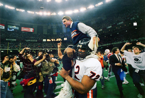 "Mike Ditka is carried off the field by William ""Refrigerator"" Perry after the Bears defeated the New Patriots to win the Super Bowl."