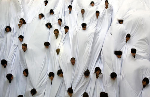 "People wearing a white cloth take part in ""Divisor"", a performance art piece by Brazilian artist Lygia Pape, during the exhibition entitled ""A Journal of the Plague Year. Fear, ghosts, rebels. SARS, Leslie and the Hong Kong story"" at Hong Kong's financial Central district."