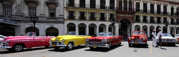 Drivers wait for customers beside U.S.-made vintage convertible cars parked in Havana May 15, 2013. Tourists can enjoy a 30-minute tour of Havana in a convertible for around $30.