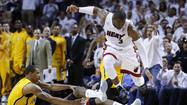 Miami Heat's Wade leaps over Indiana Pacers' Hill during their NBA Eastern Conference final basketball playoff in Miami