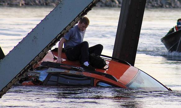 A man sits atop a car that fell into the Skagit River in Mount Vernon, Wash. Minutes earlier, a section of an Interstate 5 bridge over the river had collapsed.