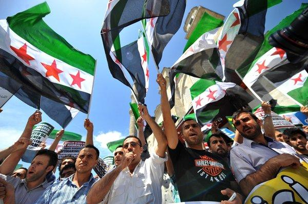 Turkish Muslim protesters wave Free Syria's flags during a demonstration held in front of the Fatih mosque in Istanbul on Friday.
