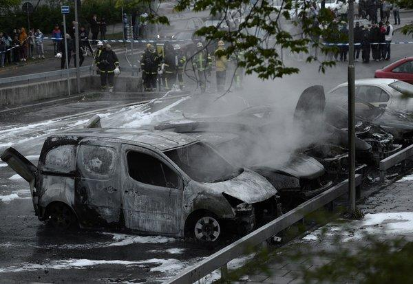 People watch as Swedish firemen extinguish burning cars in the Stockholm suburb of Rinkeby after youths rioted in several suburbs around Stockholm for a fourth consecutive night on Thursday.