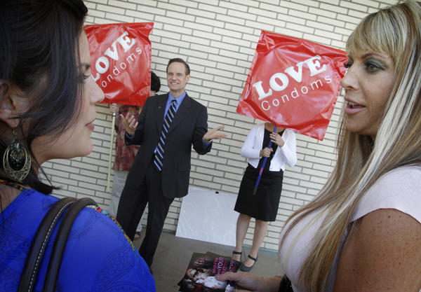Former adult film industry performers Madelyne Hernandez, left, and Shelley Lubben talk as AIDS Healthcare Foundation President Michael Weinstein addresses a small crowd in Costa Mesa about mandating that porn actors use condoms.