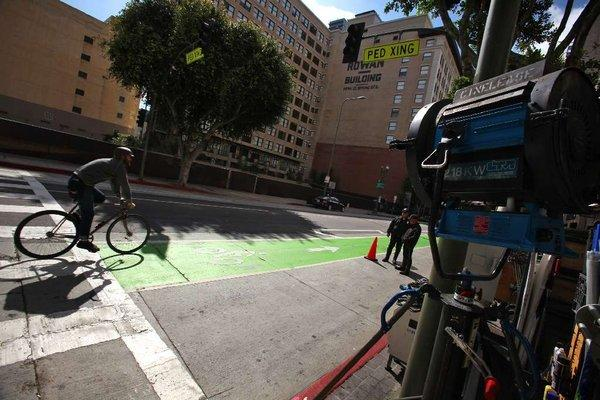 "Cyclist in green bike lane on Spring Street in downtown L.A. passes film crew working on the show ""Ringer"" last year."
