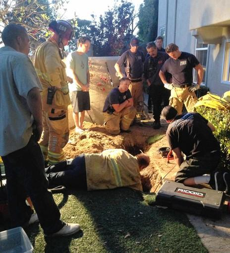 The Newport Beach Fire Department attempts to rescue a puppy that got trapped in a drainage pipe at Newport Coast home.