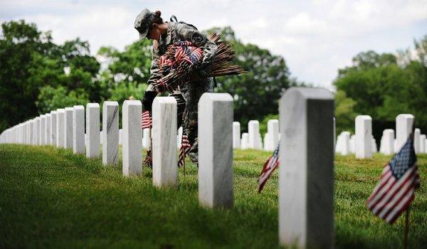 Soldier places a small American flag before each grave marker in advance of Memorial Day at Arlington National Cemetery in Virginia.