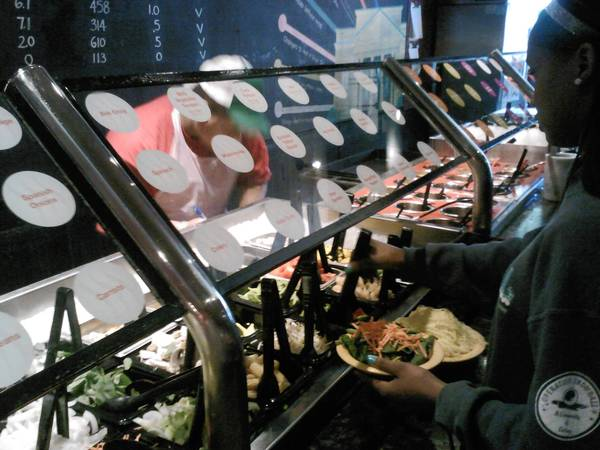 A customer chooses from the vegetable options at Flat Top Grill in Oak Park, one of the restaurants supporting residents' campaign for Meatless Mondays.