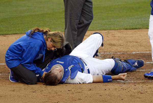 Dodgers catcher A.J. Ellis is evaluated by trainer Sue Falsone after he was knocked flat by a collision with Cardinals center fielder Jon Jay on a play at home plate in the second inning Friday night.
