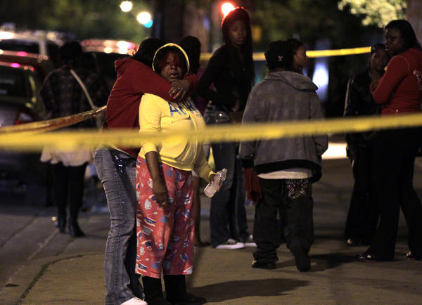 Mourners comfort each other as police investigate at the scene of a homicide in the 400 block of North Central Avenue in Chicago early Saturday morning. Two people were shot at the scene, one fatally, in one of several shooting incidents in the city overnight.