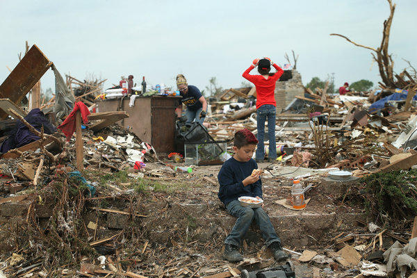 Ty Langoc takes a lunch break while helping his parents recover belongings from their house, which was destroyed by the tornado in Moore, Okla.