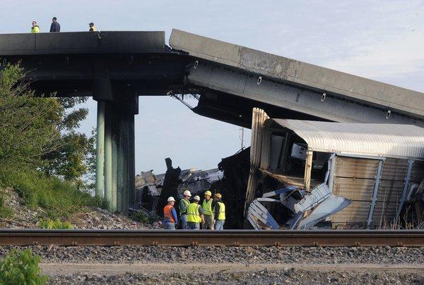 Emergency personnel investigate the Route M overpass at Rockview, Mo., about 10 miles south of Cape Girardeau, Mo., after it collapsed onto the railroad tracks. The National Transportation Safety Board has launched an investigation into the cause of a cargo train collision.