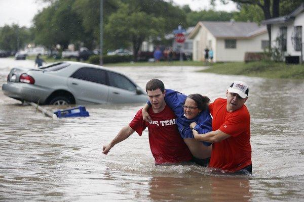 Marco Fairchild, left, and Gary Garza help Sueann Schaller from her car Saturday as floodwaters sweep San Antonio.