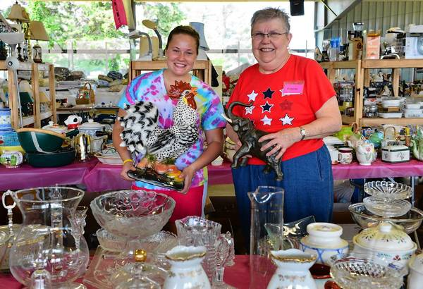 Volunteers Lindsey Hunsicker, left, and Dolores Judd, both of Bethlehem, hold up items for sale during a On The Cheap: Preview of the Boutique at the Rink rummage sale.