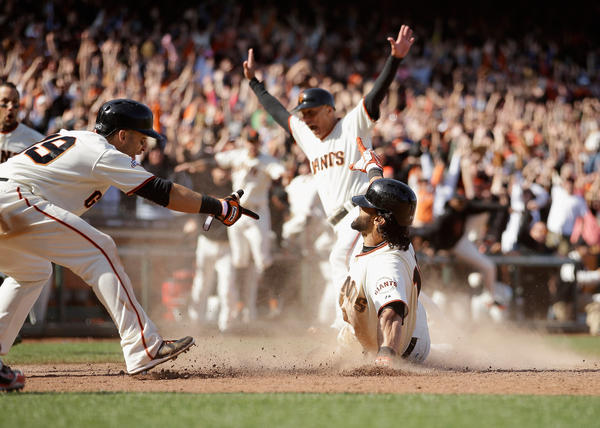 Marco Scutaro points to Angel Pagan as he slides in to home plate for a walk-off, inside-the-park home run to beat the Rockies in 10 innings.