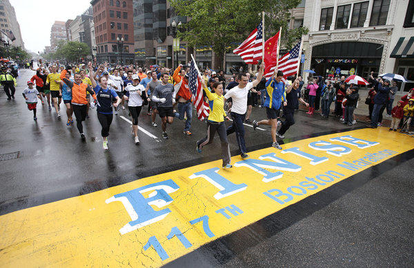 Runners who were unable to finish the Boston Marathon on April 15 because of the bombings cross the finish line on Boylston Street after the city allowed them to finish the last mile of the race in on Saturday.