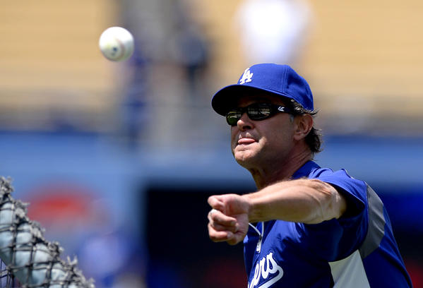 Dodgers Manager Don Mattingly pitches during batting practice before a baseball game against the St. Louis Cardinals.