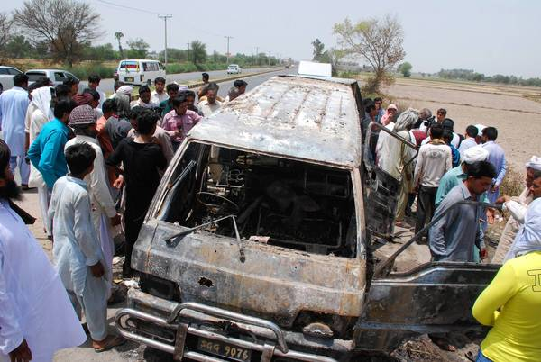 Area residents surround a school van that caught fire in Pakistan's Punjab province, killing 17 passengers.