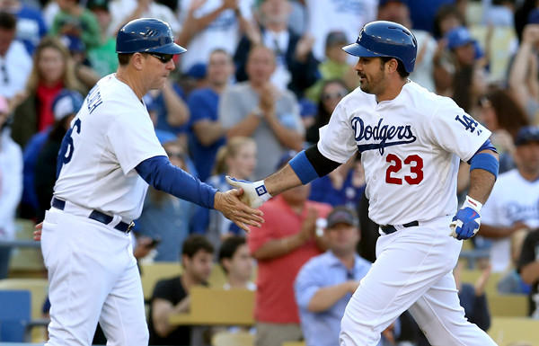 Dodgers first baseman Adrian Gonzalez (23) is congratulated by third base coach Tim Wallach after hitting a solo home run in the third inning Saturday evening.