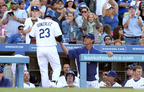 Dodgers first baseman Adrian Gonzalez is greeted by Manager Don Mattingly as he returns to the dugout after hitting a solo home run in the fifth inning against Cardinals on Saturday evening at Dodger Stadium.