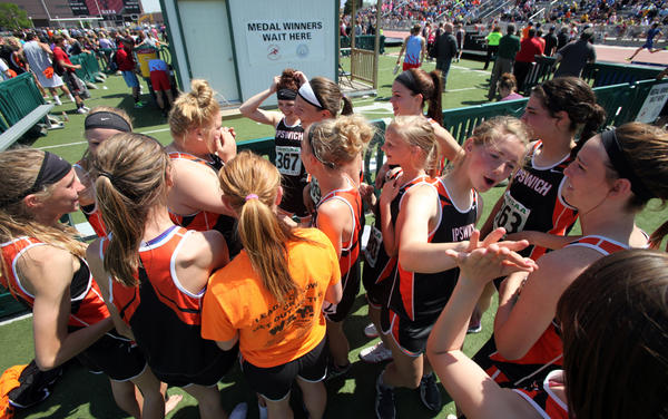 Ipswich's Kristi Pond, third from the right, high fives a teammate as another teammate Madison Kienow, fourth from the left, wipes away tears as the girls team celebrated winning their second team title in as many years Saturday at the South Dakota State Track Meet at Howard Wood Field. photo by john davis taken 5/25/2013
